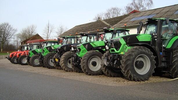 Syv traktorer i to forskellige farver solgt hos A. P. Andersen